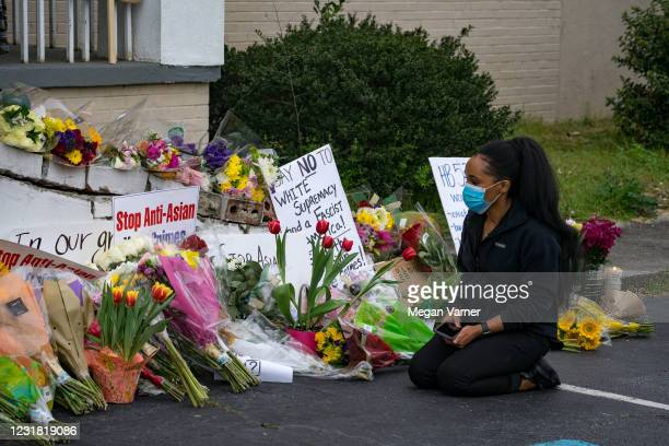 People bring flowers to the memorial sight set up outside of The Gold Spa on March 19, 2021 in Atlanta, Georgia. Mourners have gathered across the...