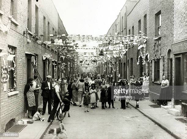 5th May 1935 Great Britain A typical street scene mirrored across the country as people gather in a working class area in Heath Street Stepney London...