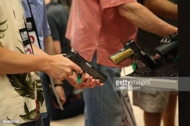 People browse firearms in an exhibit hall at the NRA's annual convention on May 4 2018 in Dallas Texas