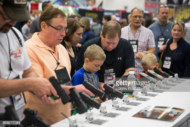 People browse firearms in an exhibit hall at the NRA's annual convention on Saturday May 5 2018 in Dallas Texas