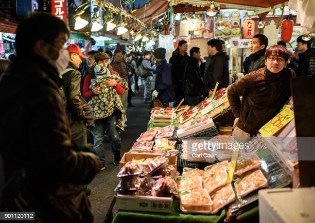 People browse food on sale at a stall in Ameya Yokocho market on January 4 2018 in Tokyo Japan Ameya Yokocho claimed to be Tokyo's last remaining...