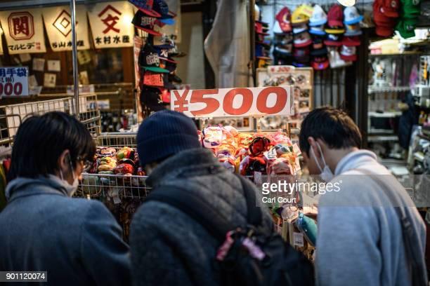 People browse items on display at a discount stall in Ameya Yokocho market on January 4 2018 in Tokyo Japan Ameya Yokocho claimed to be Tokyo's last...