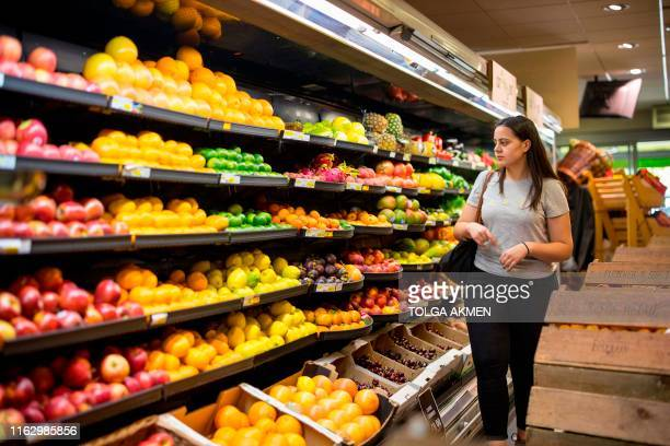 People browse the shelves with loose unpackaged fruit at Budgens supermarket in Belsize Park north London on July 2 2019 British supermarkets are...