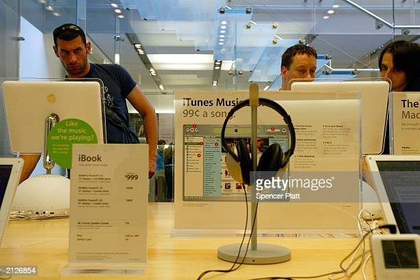 People browse through iTunes music where customers can buy songs online for 99 cents each at the Apple store June 30 2003 in New York City Last year...