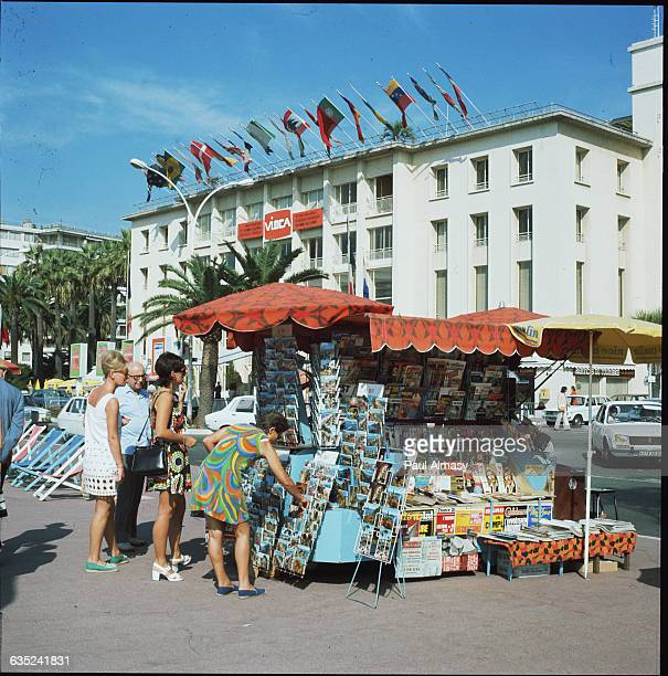 People browse through postcards at a newsstand in Cannes France A convention center is pictured in the background