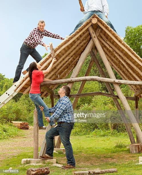 People building log hut together