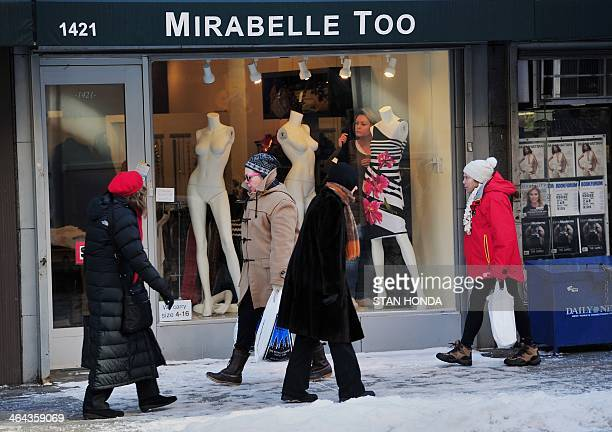 People bundled against the cold walk past a shop on Lexington Avenue on the east side of Manhattan January 22 2014 in New York The northeastern US...