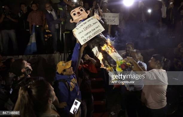 People burn an effigy depicting Guatemalan President Jimmy Morales during a protest demanding his resignation in front of the Culture Palace in...