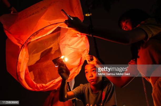 People burn flying lanterns near the North port during Chap Goh Meh celebrations to mark the end of the Chinese New Year of the Pig on February 19...