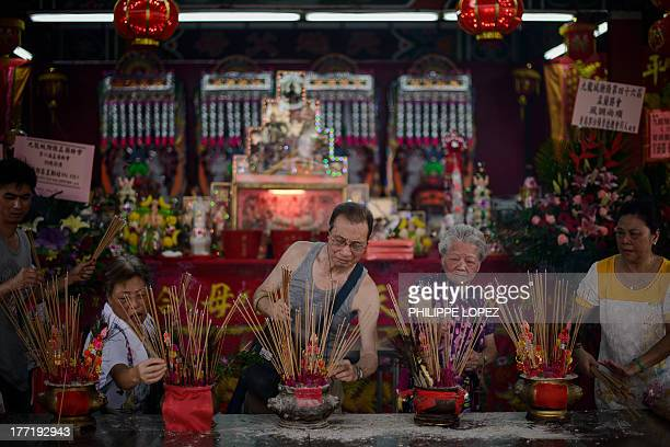 People burn incense sticks after a parade for the Hungry Ghost Festival in Hong Kong on August 22 2013 The festival celebrated in the seventh lunar...