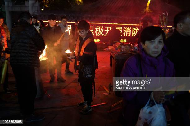 People burn incense sticks to pray for good fortune at Longhua temple in Shanghai to mark the start of the Lunar New Year early on February 5 2019...