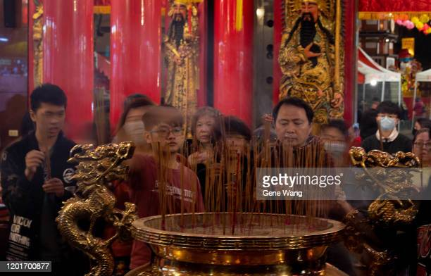 People burn incense sticks to pray for good fortune at Songshan Ciyou Temple to mark the start of the Lunar New Year early on January 25 2020 in...