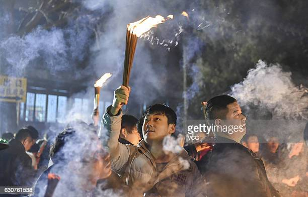 People burn incense to pray for a lucky new year at White Horse Temple on January 1 2017 in Luoyang Henan Province of China Nearly ten thousand...