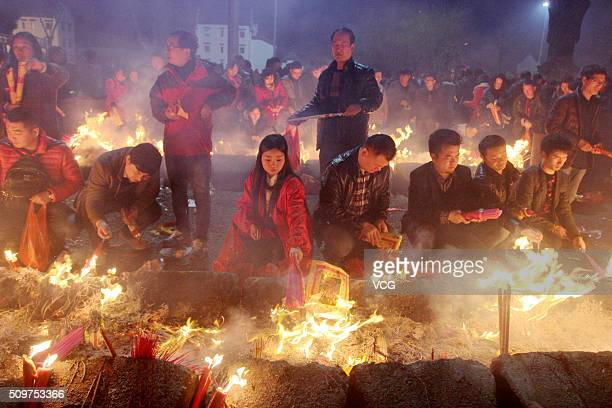 People burn incense to worship Caishen the God of wealth in China at Guiyuan Temple on February 12 2016 in Wuhan Hubei Province of China According to...