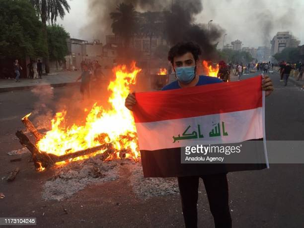 People burn tires as they gather to protest government due to corruption unsolved unemployment issue and inadequate public service in Baghdad Iraq on...