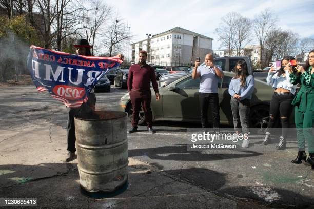 People burn Trump flags during a watch party of the televised Presidential Inauguration ceremony at Tree House Lounge on January 20, 2021 in Atlanta,...