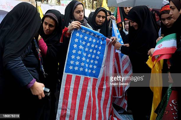 People burn US flags during a demonstration to mark the 34th anniversary of the 1979 US embassy takeover November 4 2013 in Tehran Iran Thousands of...