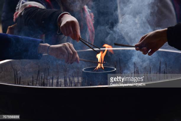 People Burning Incense Sticks In Temple
