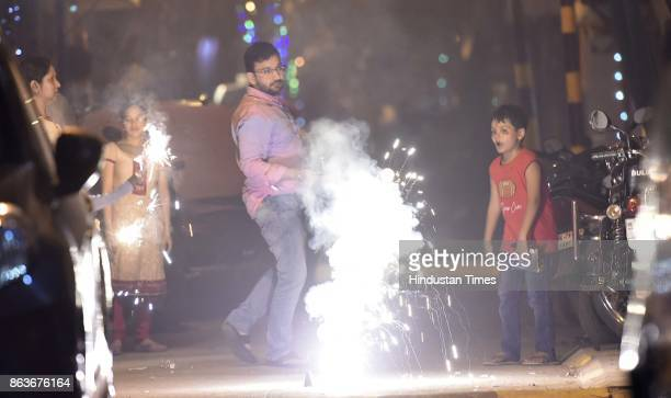 People burst firecrackers to celebrate Diwali festival despite the ban imposed by the Supreme Court of India to keep a check on air pollution on the...