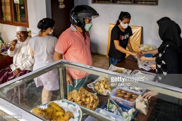 People buy breakfast at a food stall in Jakarta on April 8, 2020.
