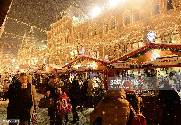 People buy Christmas gifts and Christmas Tree ornaments from stalls set up by GUM shopping mall near Red Square in Moscow Russia on December 10 2014