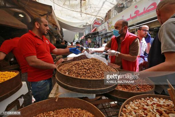 People buy dried fruits and nuts at a market ahead of the Muslim holy month of Ramadan during the novel coronavirus pandemic crisis in the Jordanian...