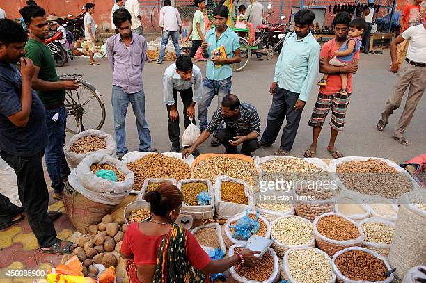 People buy dry fruits at a market ahead of the sacrificial Eid al-Adha festival on October 5, 2014 in Noida, India. Muslims across the world are...