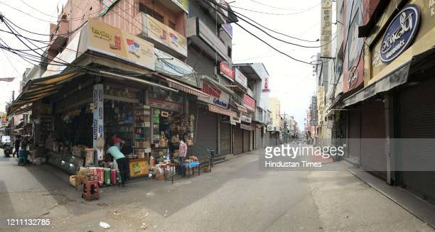 People buy essentials at a grocery store during a nationwide lockdown in the wake of coronavirus pandemic, at Sadar Bazar near Sohna chowk, on April...