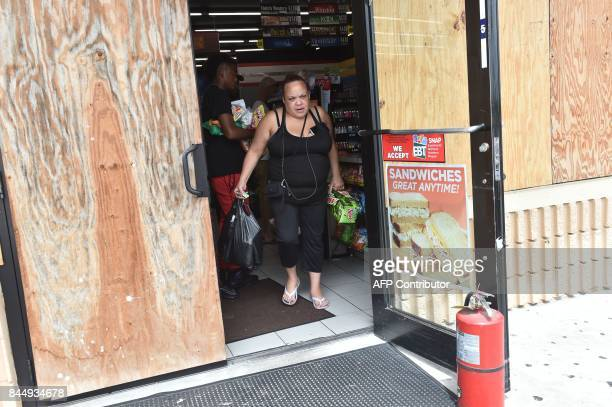 People buy food in a supermarket in Port Charlotte Florida on September 9 2017 Hurricane Irma weakened slightly to a Category 4 storm early Saturday...