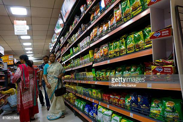 People buy food products from shelves of a big supermarket