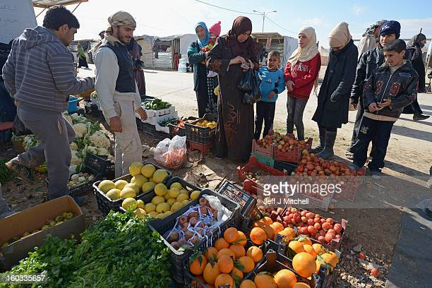 People buy fruit and vegetables as Syrian refugees go about their daily business in the Za'atari refugee camp on January 29 2013 in Mafraq Jordan...