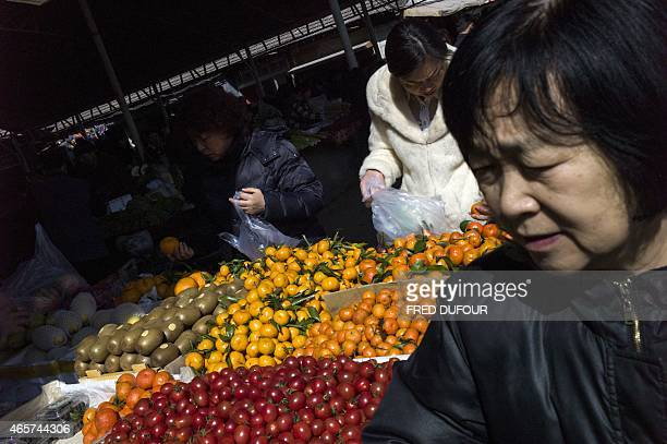 People buy fruits and vegetables at a market in Beijing on March 10 2015 China's consumer inflation rebounded in February from a morethanfiveyear low...
