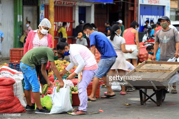 People buy fruits outside of Belen Market on May 06, 2020 in Iquitos, Peru. Iquitos, capital city of the largest province of Peru, is about to...