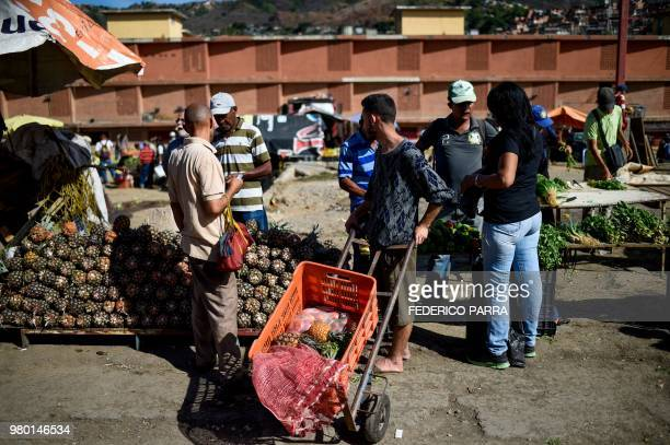 People buy groceries at the municipal market of Coche a neighbourhood of Caracas on June 20 2018 Venezuelan President Nicolas Maduro ordered the...