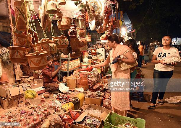 People buy idols of Goddess Lakshmi and Lord Ganesha from roadside stalls for the Diwali festival on October 29 2016 in New Delhi India Diwali is one...