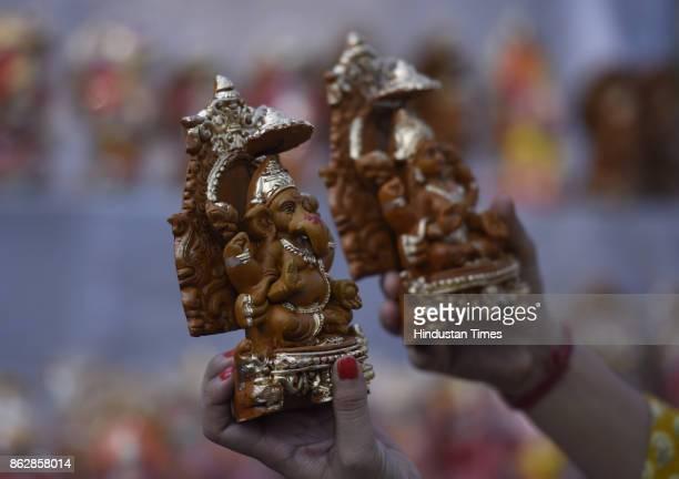 People buy idols of Goddess Lakshmi and Lord Ganesha from roadside stalls for the Diwali festival at Sarojini Nagar Market on October 18, 2017 in New...