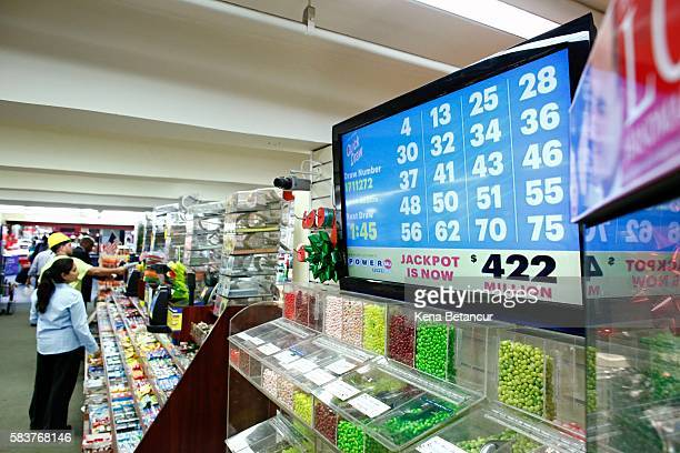 People buy lottery tickets at a store in Penn Satation on July 27 2016 in New York City The Powerball drawing on Wednesday will give lottery players...