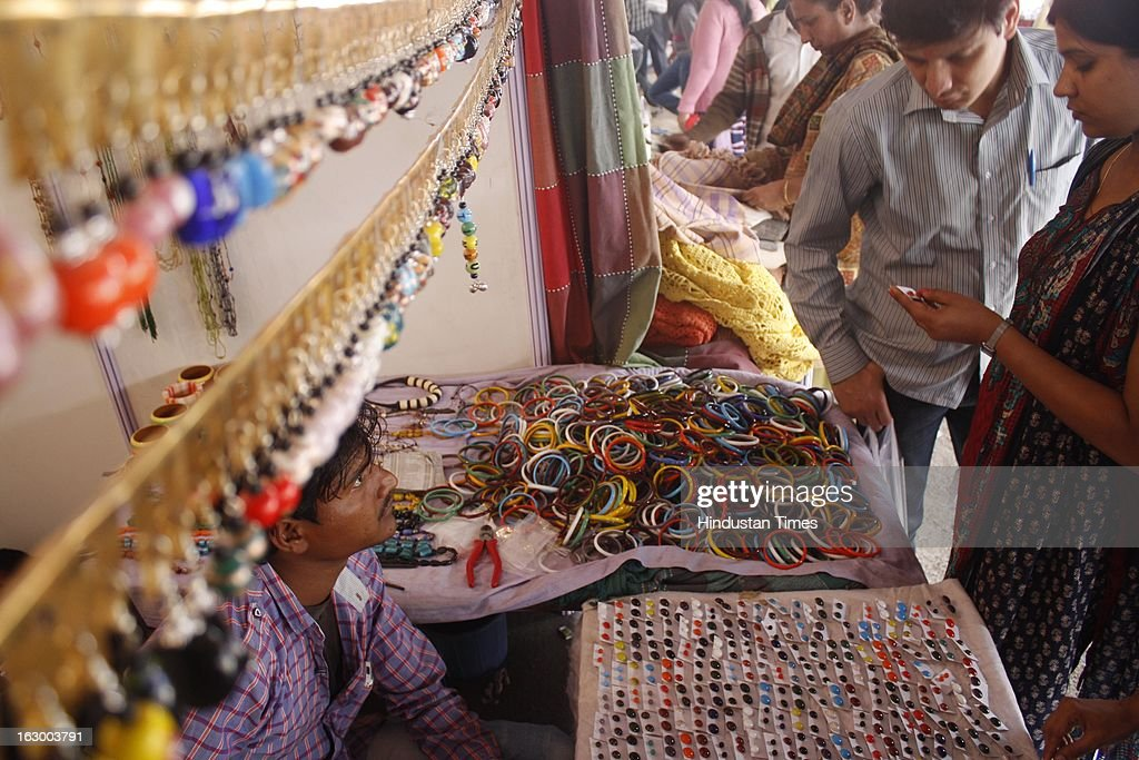 People buy products from a stall during the final day of Basant Utsav exhibition at Ramlila Ground Noida Stadium in Sector 21A on March 3, 2013 in Noida, India. Handmade products of different states are displayed on sale in the exhibition.