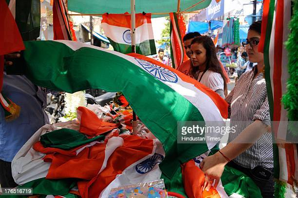 People buy tricolors from a roadside vendor on the eve of Independence Day on Wednesday August 14 2013 in Noida India Security personnel are on...