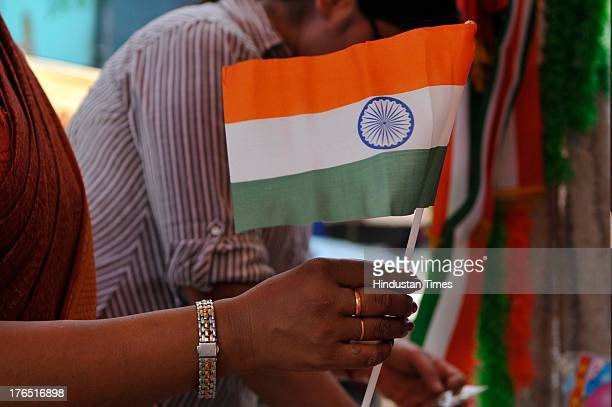 People buy tricolors from a roadside vendor on the eve of Independence Day on Wednesday, August 14, 2013 in Noida, India. Security personnel are on...