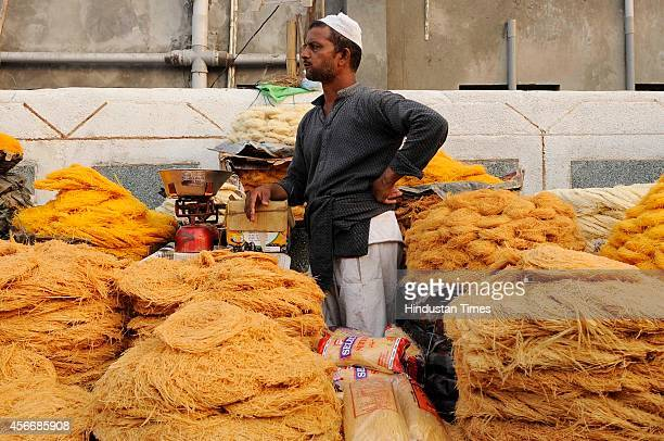 People buy vermicelli at a market ahead of the sacrificial Eid al-Adha festival on October 5, 2014 in Noida, India. Muslims across the world are...