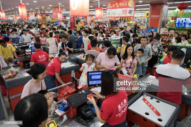 People buy water and food at a supermarket ahead of the arrival of the Super Typhoon Mangkhut in Zhanjiang in Guangdong province on September 15 2018