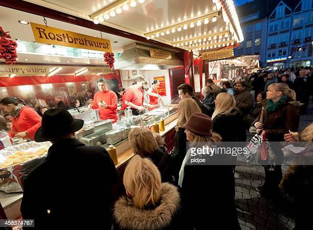 Leute kaufen bratwurst am Weihnachtsmarkt in Düsseldorf, Deutschland