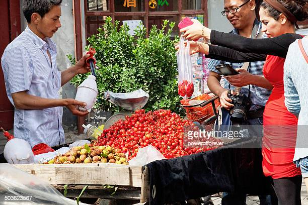 Leute kaufen Obst und Gemüse vom Straßenverkäufer