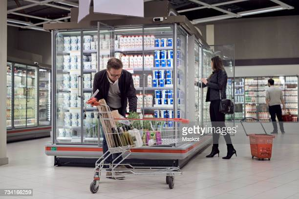 people buying groceries at refrigerated section in supermarket - retail display stock pictures, royalty-free photos & images