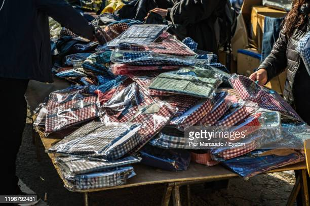 people buying shirts in market - street market stock pictures, royalty-free photos & images