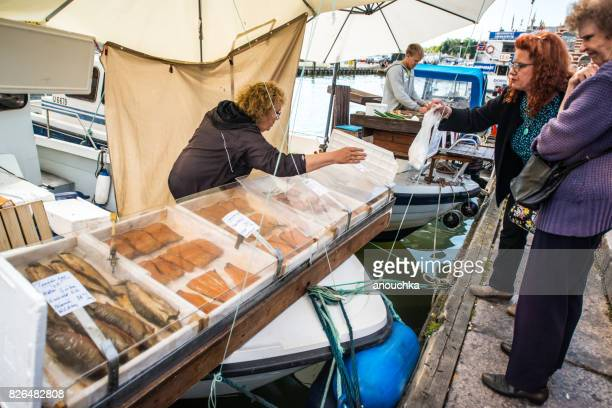 People buying smoked fish from boats on Market Square, Helsinki, Finland