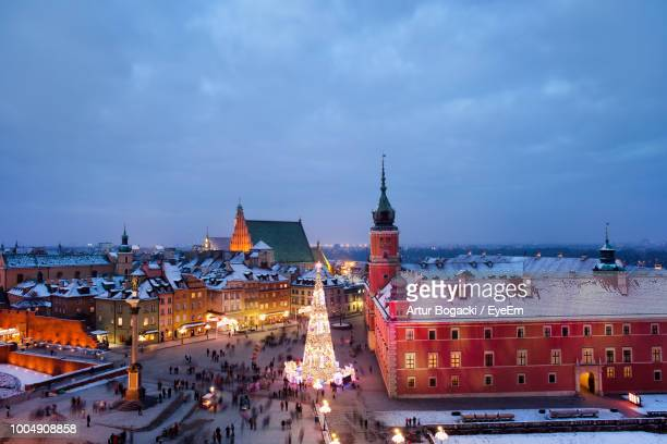 people by decorated illuminated christmas tree by church at town square against sky - warsaw stock pictures, royalty-free photos & images