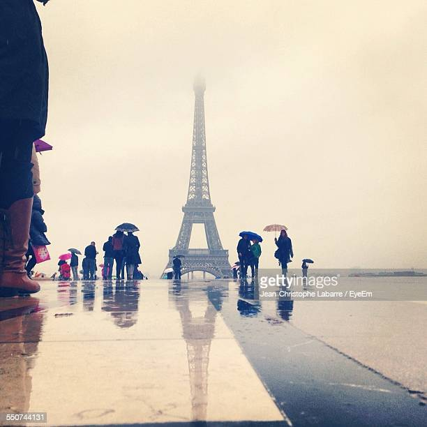 People By Eiffel Tower Against Sky During Rainy Season