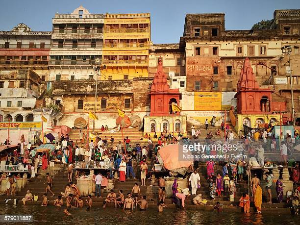 people by ganges river against building - varanasi stock pictures, royalty-free photos & images
